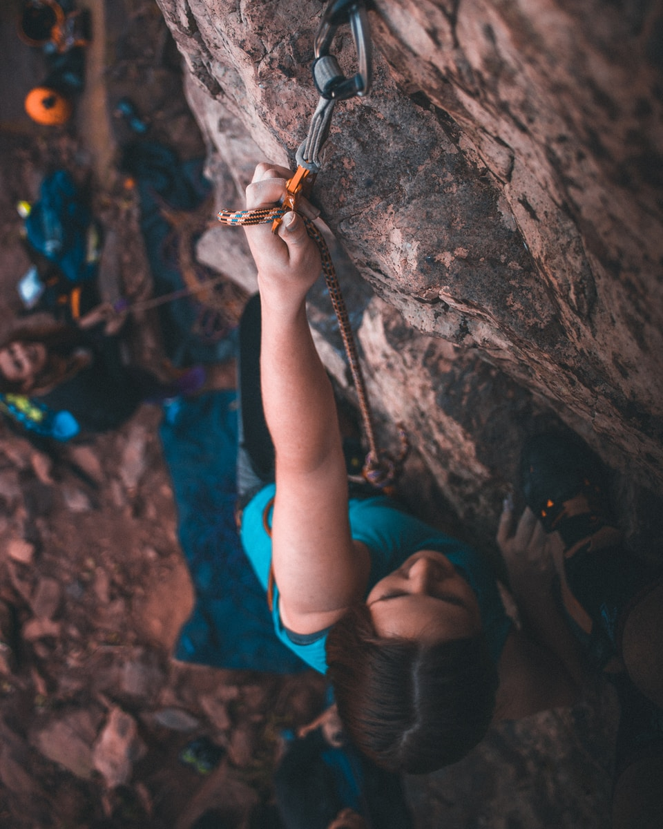 woman in black leather boots climbing on brown rock